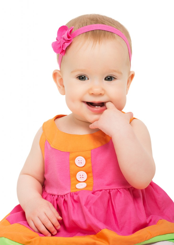 happy little sly baby girl in bright multicolored festive dress isolated on a white background